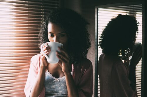 Woman sipping coffee by the window, contemplating life
